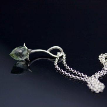 Ett silverhänge, en vattendroppe. A silver pendant, a drop of water.