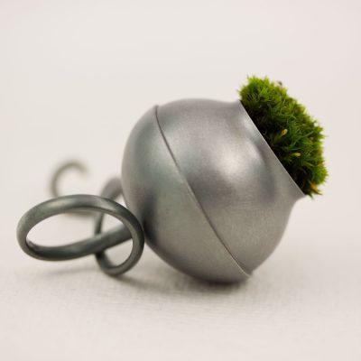 En ring av oxiderat silver, en behållare för mossa, en påminnelse om skogen, en trygg värd att bära med sig.