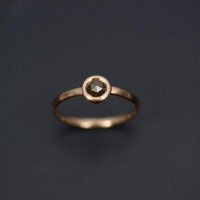 En ring som kan användas som vigselring om man vill. Här i 18k rödguld med en gröntonad rosenslipad diamant.