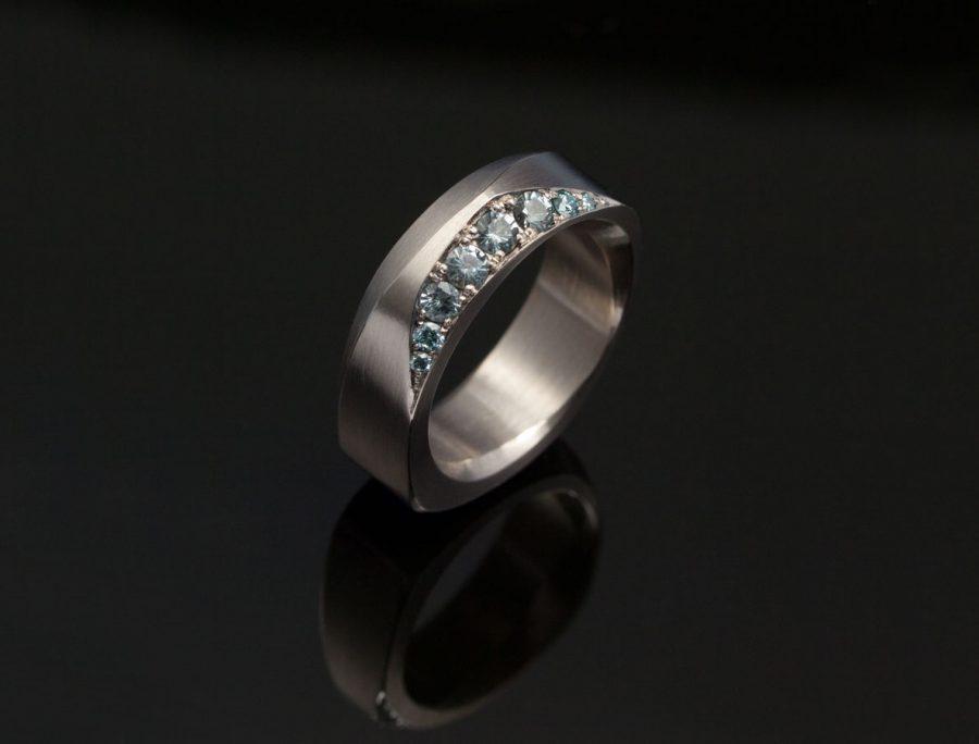 En geometrisk vigselring i vitguld med etiska blå saffier och små blå diamanter satta med fadenfattning.