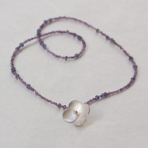 Halsband med en ensam silver blomma med rosa sötvattenpärla på en collier av ametist och tanzanit.